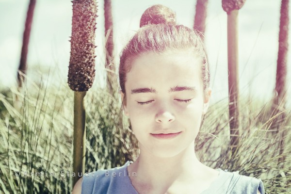 vintage version of a teenager girl meditates in front of a reed